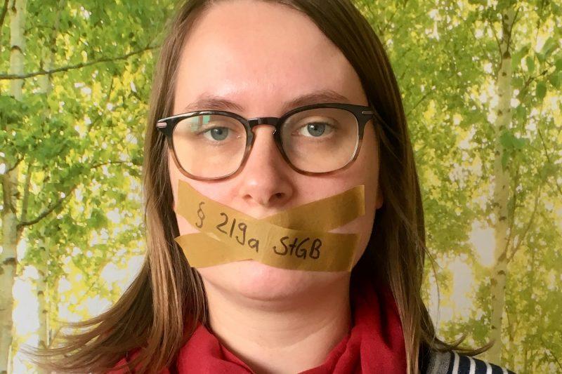 """Mareike Engels hat den Mund zugeklebt. Die Klebestreifen tragen die Beschriftung """"§ 219a StGB"""""""