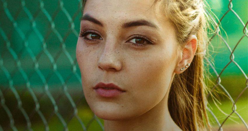 Motiv: junge Frau mit ernstem Blick; Text: Gegen Gewalt an Frauen - Starker Schutz für alle Frauen!